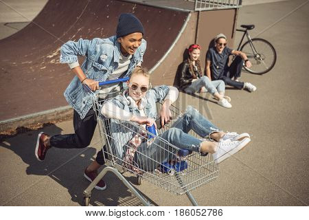 Boy Carrying Happy Girl In Shopping Cart While Friends Sitting Near Ramp At Skateboard Park