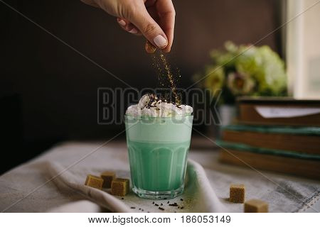 Woman decorate with colored edible sparkles green mint coffee. Milk shake cocktaill frappuccino. Unicorn coffee unicorn food.