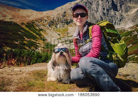 Young woman tourist with dog and sunglasses sitting on high mountains background