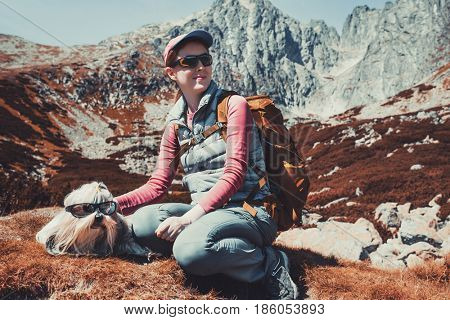 Young woman tourist with dog and sunglasses sitting on high mountains background. Autumn white and red colors.