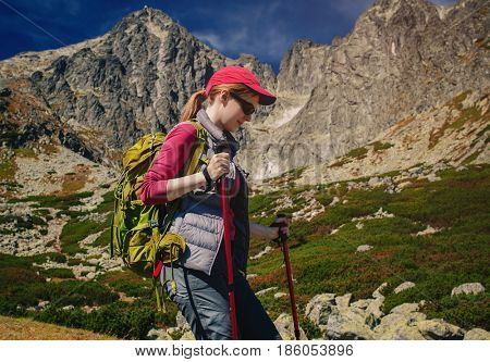 Young woman tourist with green backpack and sunglasses walking on mountains background