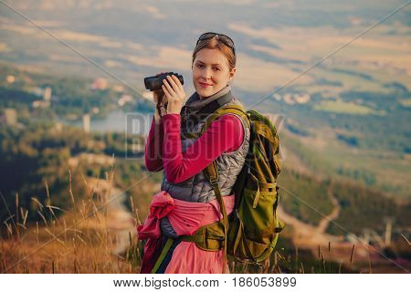 Young woman tourist standing with binoculars on mountain portrait