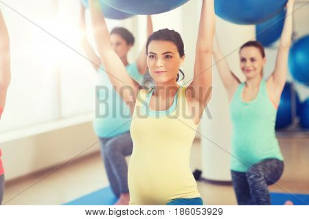 pregnancy, sport, fitness, people and healthy lifestyle concept - group of happy pregnant women exercising with ball in gym