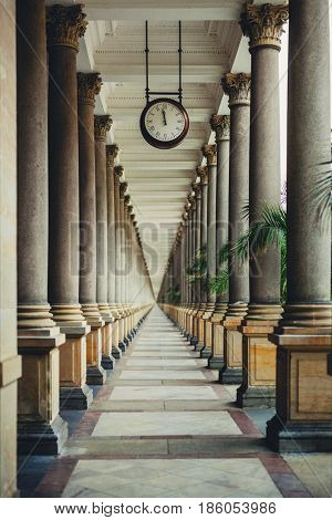 Infinite perspective with classic columns and clock in front. Architecture concept.