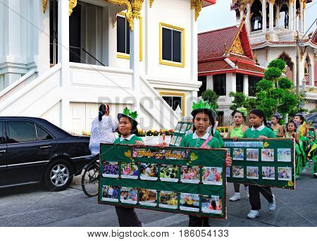 Bangkok, Thailand - January 8, 2016: Pupils of the Elementary School of Wat Chana Songkhram carry pictures during festive procession through the streets of the city.