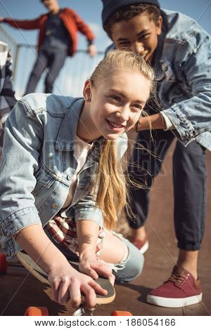 Friend Helping Stylish Hipster Girl Riding Skateboard, Teenagers Having Fun Concept