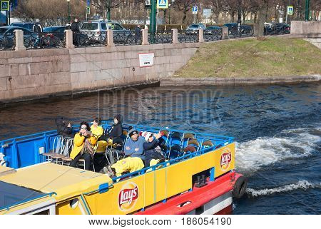 SAINT - PETERSBURG, RUSSIA - MAY 11, 2017: Asian tourists on the excursion boat take pictures of sights along the Moika River near The Second Garden Bridge