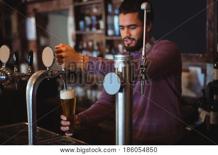 Bar tender filling beer from bar pump at bar counter