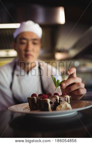 Close-up of male chef garnishing dessert plate in commercial kitchen