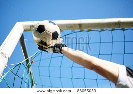 sport and people - soccer player or goalkeeper hand catching ball at football goal over blue sky