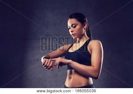 sport, fitness, technology and people concept - young woman with heart-rate watch in gym
