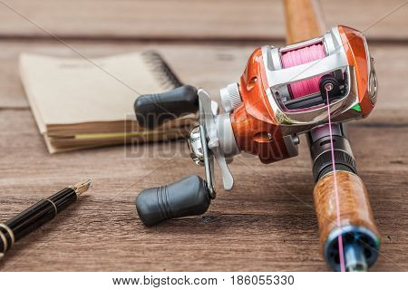 Fishing tackle - Baitcasting Reel book on wooden background
