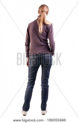 back view of standing young beautiful  blonde woman in sweater. girl  watching. Rear view people collection. thoughtful girl expecting that looks into the distance while standing back to us