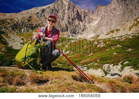 Young woman tourist with big green backpack and poles standing on high mountains background