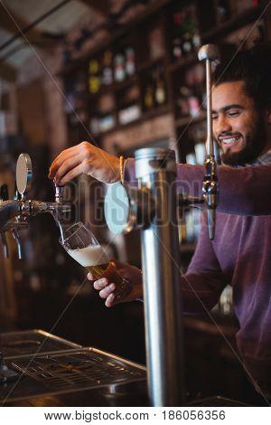 Bar tender filling beer from bar pump at bar counter
