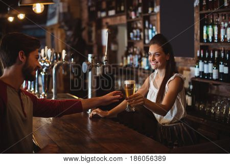 Female bar tender giving glass of beer to customer at bar counter