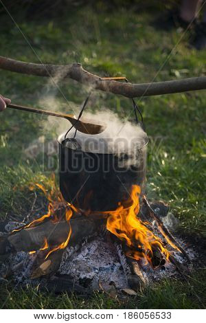Back pot are heating under fire. Somebody are holding big wood spoon under pot. Scene from travel.