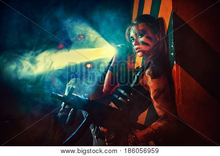 Young strong woman warrior with gun and flashlight in dramatic urban night scene