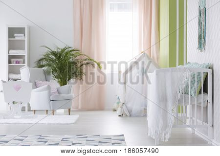 White modest interior of baby room with cradle