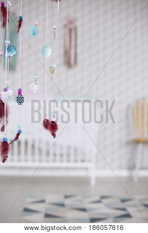 Colorful boho decoration in simple and modest white baby room