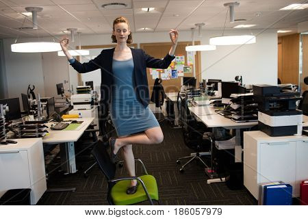 Full length of businesswoman practicing yoga while standing on chair at office