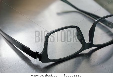 COLOR PHOTO OF PLASTIC FRAME GLASSES ON STEEL TABLE
