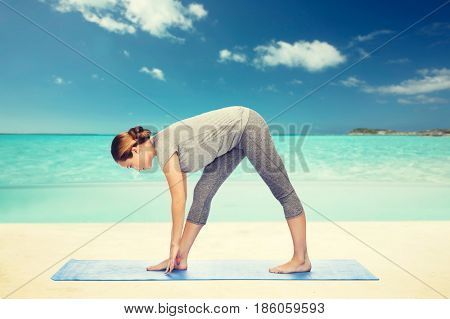 fitness, sport, people and healthy lifestyle concept - woman making yoga intense stretch pose on mat over beach background