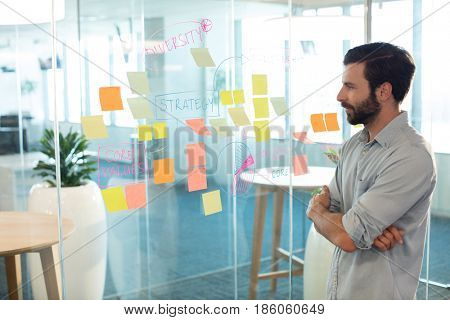 Young businessman looking at adhesive notes on glass at office