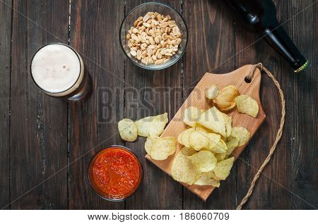 glass and bottle of dark beer with crumbs of chips on wooden table. Top
