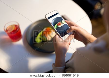 food, new nordic cuisine, technology and people concept - woman with smartphone photographing toast skagen with shrimps, caviar and buttery bread at restaurant