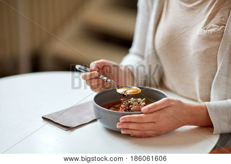 food, new nordic cuisine and people concept - woman eating vegetable pumpkin-ginger cream soup with goat cheese and tomato salad with yogurt in bowl at cafe or restaurant