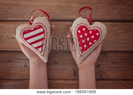 Child Holding Red Textile Heart In Hands Over A Wooden Table.