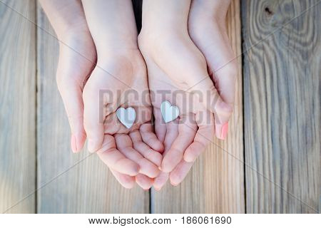Child And Mother's Hands Holding Heart