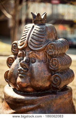 Khabarovsk Russia - May 9 2017: Funny cartoon king wearing a wig and a crown bronze statue. Fairy tale character metal sculpture face close-up. Chubby Caucasian royal person head