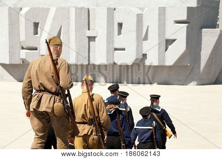 Group of soldiers and sailors wearing old retro USSR military uniform. Russian Victory Day celebration on May 9 at memorial 1941-1945 text on the background. Great Patriotic War reenactment