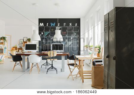 New design office with white wall and blackboard calendar