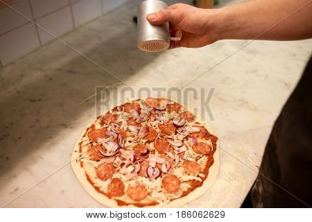 food, culinary, italian cuisine, people and cooking concept - cook hand adding pepper to salami pizza at pizzeria