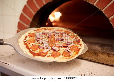 food, italian kitchen, culinary, baking and cooking concept - peel placing pizza into oven at pizzeria