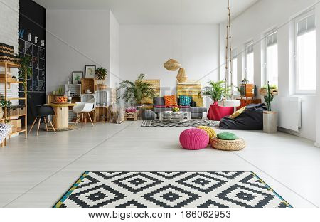 White living room with colorful pouf pattern carpet crate furniture