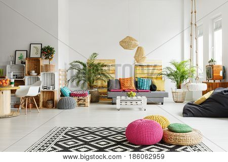 Loft living room with colorful poufs sofa carpet crate furniture