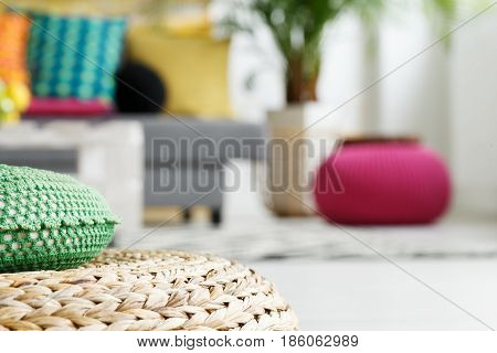 Interior with rattan cushion pink and green pouf close up