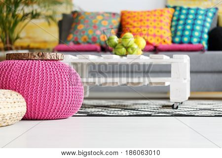 Interior with pink pouf colorful cushions grey couch diy table