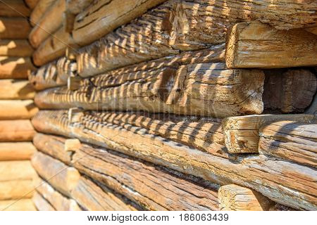 Details of log cabin corner joint with round logs and wall of wooden house at sunny spring day, Moscow, Russia
