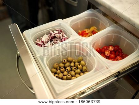 cooking, storage and food concept - containers with olives, chopped cherry tomatoes and red onion at restaurant kitchen