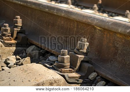 Old rusty screw - iron bolts on railway. Rusty part of the railway