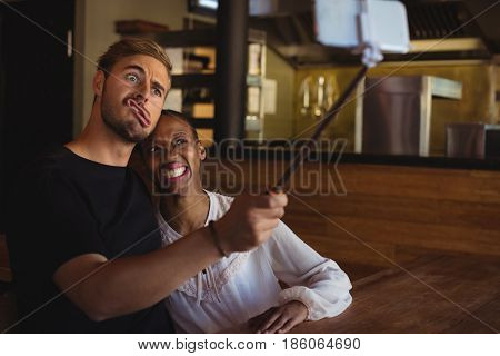Happy couple taking selfie from mobile phone in restaurant