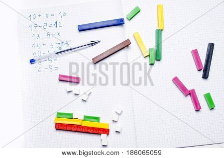 Open exercise book with colored plastic math learning tools number rods on white background. Elementary school concept.