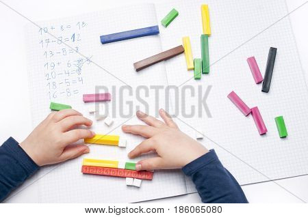 Open exercise book with colored plastic math learning tools number rods on white background. Close-up of children's hands. solving mathematics examples. Educational and school concept.