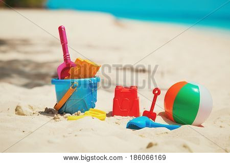 kids toys on tropical sand beach, vacation concept