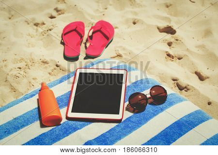 Vacation accesssories - suncream, flip-flops and touch pad on beach